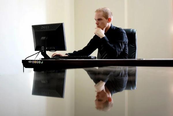 Hombre en su oficina mirando su ordenador