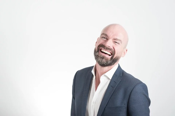 Hombre con smoking sonriente fondo blanco