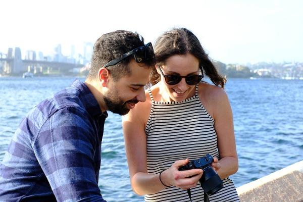 Como romper el hielo con una chica, pareja al aire libre viendo fotos en una cámara